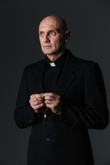 Portrait of handsome priest standing and holding rosary