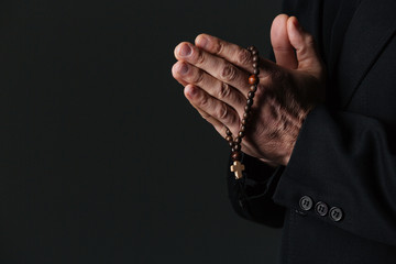 Hands of priest holding rosary and praying