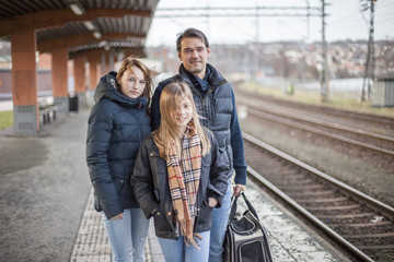 Portrait of father with daughters at train station
