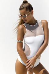 Woman in white swimsuit and golden sunglasses with hair up poses on isolated background. High fashion shot.