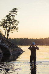 Swimmer standing in water at sunset