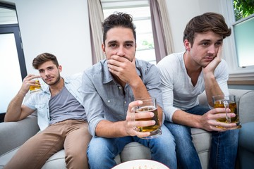 Upset male friends drinking alcohol while watching TV