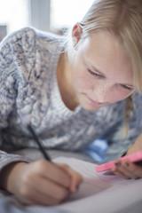 Teenage girl writing on bed