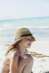 Smiling girl crouching on beach by sea