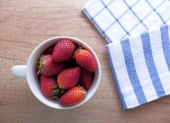 kitchen still life with strawberries in white pottery cup and dishcloths on vintage wooden table