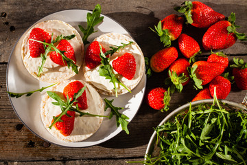 Multigrain rice cakes with strawberries fruit , soft mascarpone cheese and arugula for healthy breakfast.