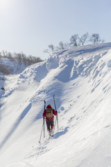 Man carrying skies up snowy slope