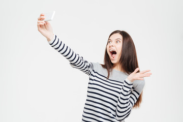 Funny woman making selfie photo on smartphone