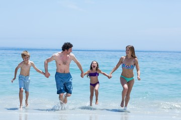 Family holding hands while running in shallow water