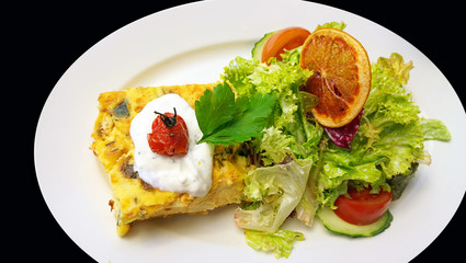 Quiche and salad topped by an orange slice, white saucer isolate on black