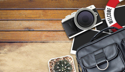 camera and blank photo frames on wooden table. top view, travel concept