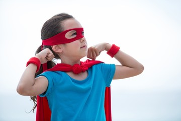 Girl in superhero costume flexing muscles