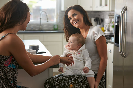 Female couple sitting in the kitchen with baby girl on knee