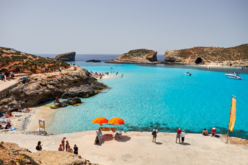 BLUE LAGOON, COMINO, MALTA - APRIL 13, 2016. People enjoy blue lagoon  with crystal clear blue water.