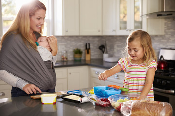 Mum holding baby watches older daughter preparing food