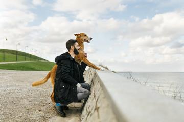 Man and his dog looking at the sea