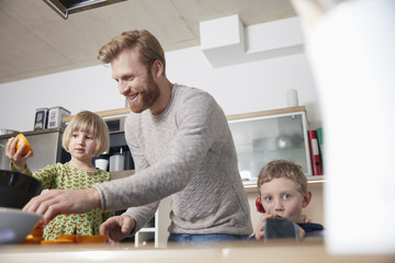 Father and children using juice squeezer in kitchen