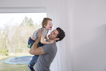 Happy father lifting laughing son