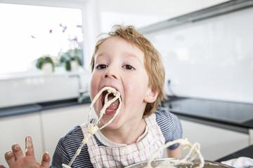 Boy licking dough off mixer