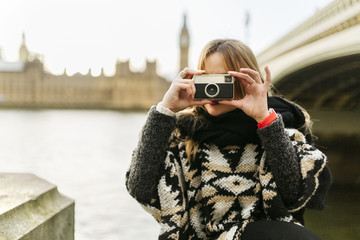 UK, London, young woman taking a picture near Westminster Bridge