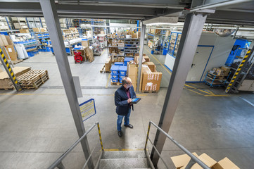 Manager checking goods in storage hall of factory