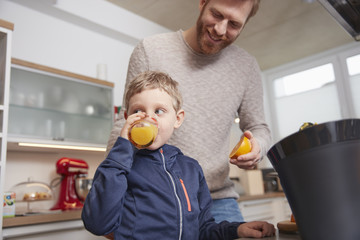 Father with son drinking feshly squeezed orange juice in kitchen