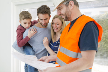 Construction worker explaining family the construction plan