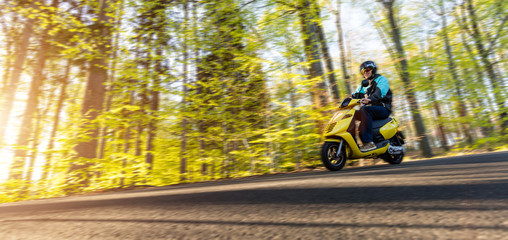 Young man driving scooter, blur motion