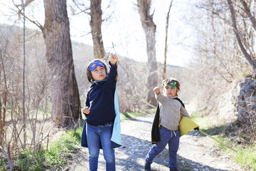 Two little boys dressed up as a superheros posing on a path