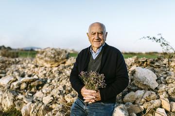 Spain, Tarragona, senior man with bouquet of flowers