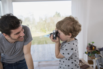 Father and son playing with camera