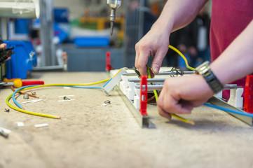 Worker cutting wires on workbench