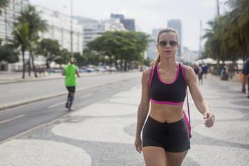 Brazil, Rio de Janeiro, sportive woman walking on pavement