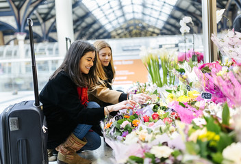UK, London, Two young women admiring flowers at train station