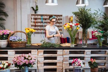 Fototapeta Cute concentrated female florist working in flower shop obraz