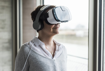 Woman wearing virtual reality glasses and headphones