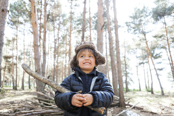 Portrait of little boy playing with branch in the woods