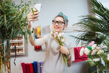 Happy woman florist taking selfie with smartphone in flower shop