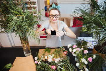 Happy woman taking photos of flowers on table in shop