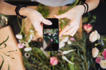Woman florist taking pictures of flowers with mobile phone