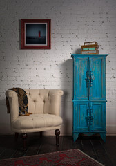 Retro composition of classic beige armchair, vintage blue cupboard, ornate scarf and framed painting in studio