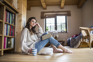 Young woman at home reading a book