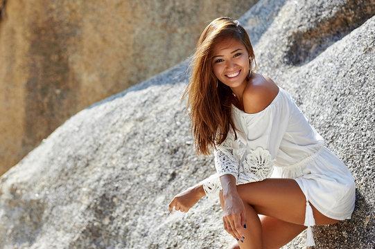Cute pretty tanned slim girl in white dress on the beach