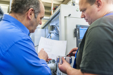 Two men discussing a metal workpiece