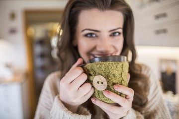 Young woman at home drinking cup of coffee in kitchen