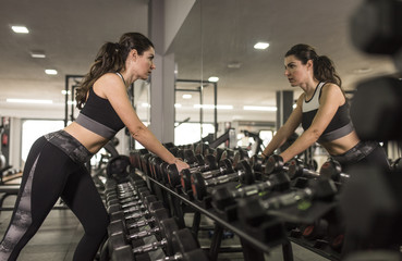 Mature woman ready for lifting dumbbells in gym
