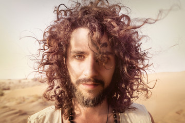Portrait of man with beard and curly hair in the desert