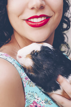Back view of young woman with Guinea pig on her shoulder