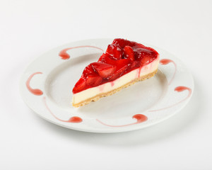 Delicious cheesecake with strawberry jelly and jam on the plate on white background. Close up side view.