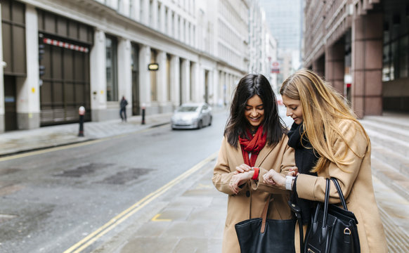 UK, London, Two friends exploring the city, checking smart watches